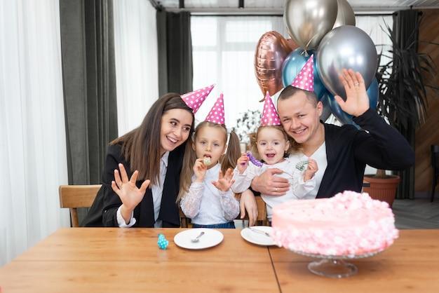 Geburtstagsfeier und familie in feiertagshüten am tisch winken in der kamera. rosa kuchen und luftballons.
