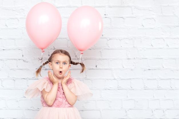 Geburtstagsfeier verspottet überraschtes ausdruckskindmädchen mit starken emotionen, das auf wandhintergrund posiert