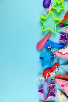 Geburtstagsfeierkappen, -ballon und -sterne auf blauem hintergrund.