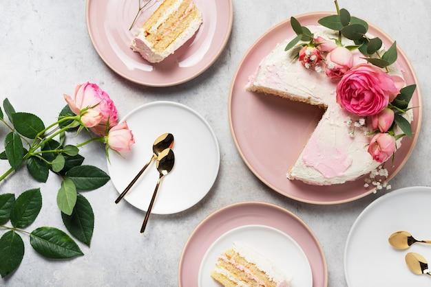 Geburtstagsfeierkonzept mit rosafarbenem weißen kuchen verziert mit rosa rosen, ansichtbild von oben nach unten