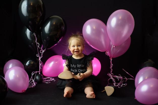 Geburtstagsfeiertag des ersten jahres des mädchens. ballons und urlaub drinnen. kindergeburtstag. kleines hübsches mädchen in ihrem ersten schwarzen kleid