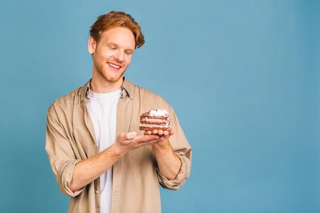 Geburtstagsfeiertagskonzept! porträt eines fröhlichen jungen glücklichen mannes, der einen geburtstagskuchen hält