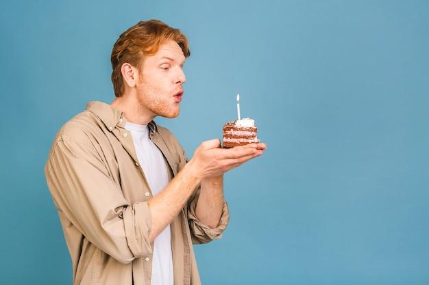 Geburtstagsfeiertagskonzept! porträt eines fröhlichen jungen glücklichen mannes, der einen geburtstagskuchen mit kerze hält