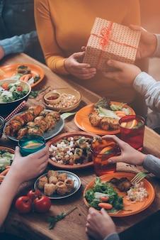 Geburtstagsgeschenk. draufsicht auf eine gruppe von menschen, die zusammen zu abend essen, während der mann den frauen eine geschenkbox gibt