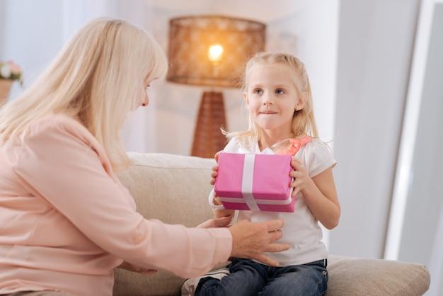 Geburtstagsgeschenk. freudiges nettes süßes mädchen, das lächelt und eine geschenkbox hält, während es mit ihrer großmutter zusammen ist