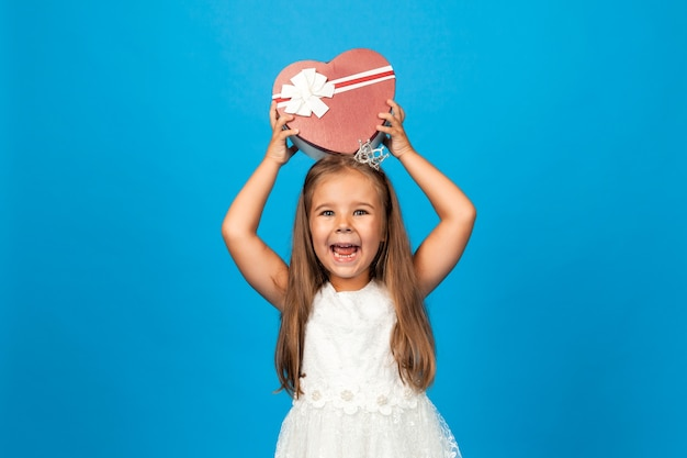 Geburtstagsgeschenk für kinder. überraschungs- und geschenkbox. kleines mädchen, das eine schachtel mit einem geschenk hält.