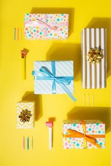 Geburtstagsgeschenke. attribute des kerzenurlaubs auf kuchen und pfeife. gelber hintergrund, harte schatten