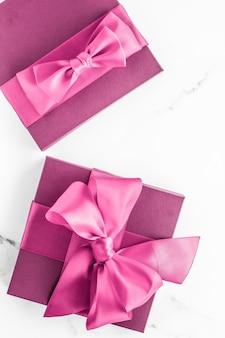 Geburtstagshochzeit und girly branding-konzept rosa geschenkbox mit seidenschleife auf marmorhintergrund mädchen-baby-dusche-geschenk und glamour-mode-geschenk für luxus-beauty-marken-ferien-flatlay-kunstdesign Premium Fotos