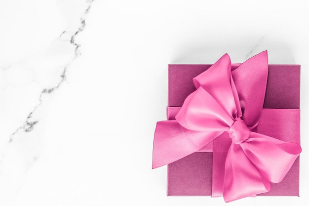 Geburtstagshochzeit und girly branding-konzept rosa geschenkbox mit seidenschleife auf marmorhintergrund mädchen-baby-dusche-geschenk und glamour-mode-geschenk für luxus-beauty-marken-ferien-flatlay-kunstdesign