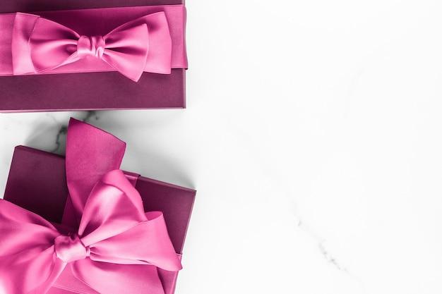 Geburtstagshochzeit und girly branding-konzept rosa geschenkbox mit seidenschleife auf marmorhintergrund mädchen-baby-dusche-geschenk und glamour-mode-geschenk für luxus-beauty-marken-ferienwohnungsdesign