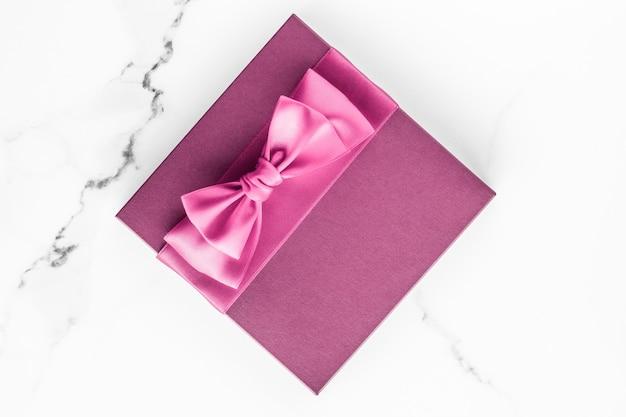 Geburtstagshochzeit und mädchenhaftes branding-konzept rosa geschenkbox mit seidenschleife auf marmoroberfläche mädchen-baby-dusche-geschenk und glamouröses modegeschenk für luxus-beauty-marken-feiertags-flatlay-kunstdesign