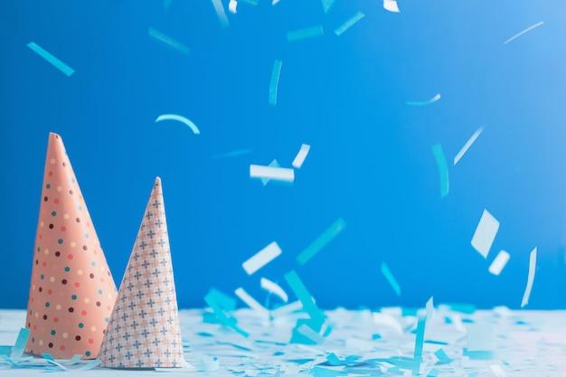 Geburtstagshut und konfetti auf blauem hintergrund