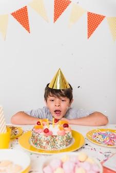 Geburtstagsjunge, der kerzen auf kuchen durchbrennt