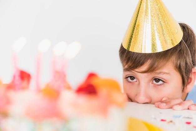 Geburtstagsjunge im partyhut, der seinen kuchen schaut