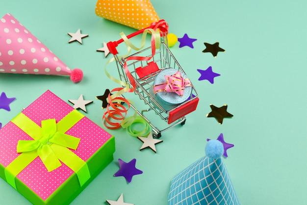Geburtstagskappen und ein geschenk, konfetti auf einem grünen hintergrund. platz für text oder design.