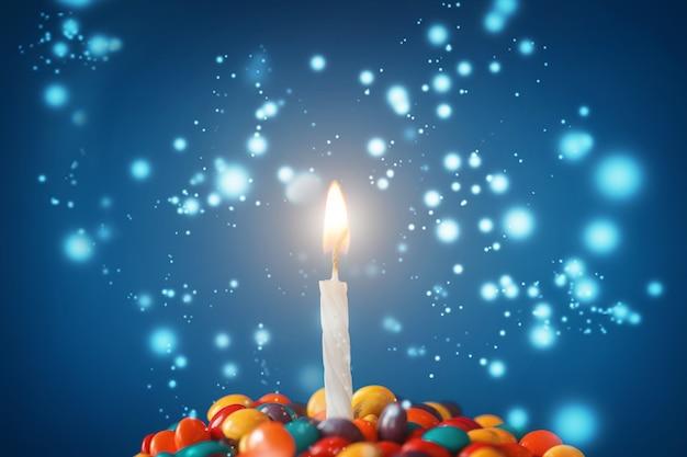 Geburtstagskerze auf köstlichem kleinem kuchen mit süßigkeiten auf hellblauem hintergrund. feiertagsgrußkarte