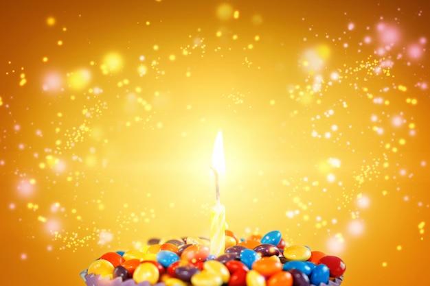 Geburtstagskerze auf köstlichem kleinem kuchen mit süßigkeiten auf hellgelbem hintergrund. feiertagsgrußkarte