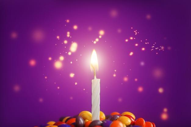 Geburtstagskerze auf köstlichem kleinem kuchen mit süßigkeiten auf hellpurpurnen hintergrund. feiertagsgrußkarte