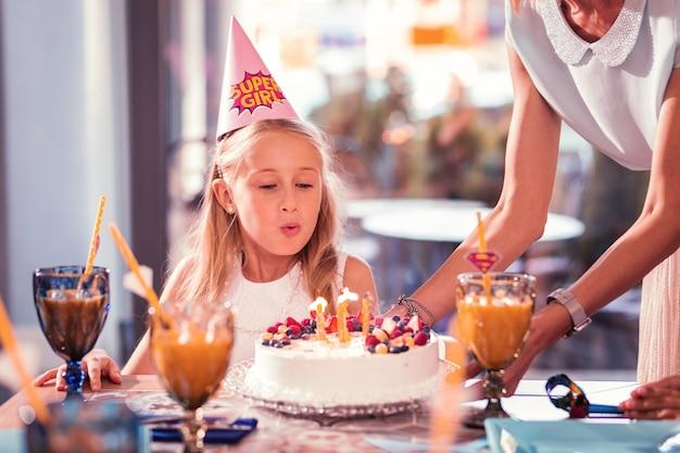 Geburtstagskind, das einen wunsch macht und kerzen bläst