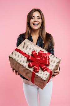 Geburtstagskind, das ihre große geschenkbox mit roter schleife zeigt