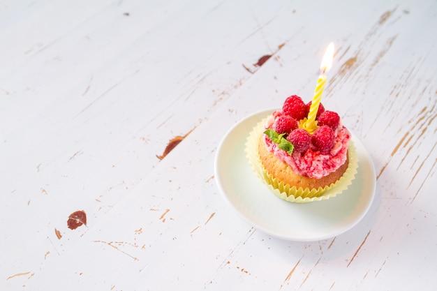 Geburtstagskleiner kuchen mit himbeere und süßigkeit