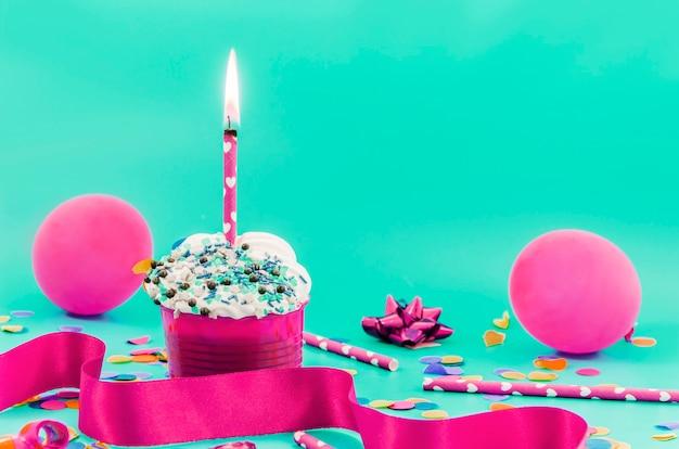 Geburtstagskleiner kuchen mit kerze und ballonen