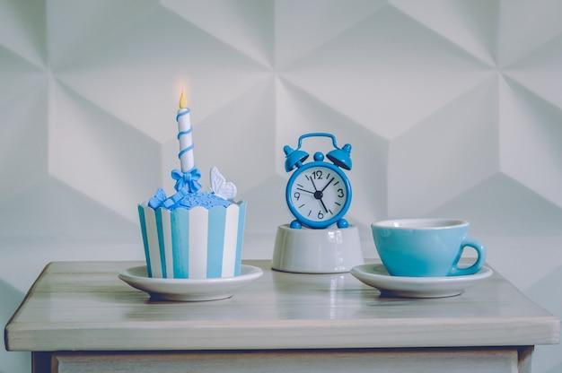 Geburtstagskleiner kuchennachtisch mit blauem wecker und tasse tee