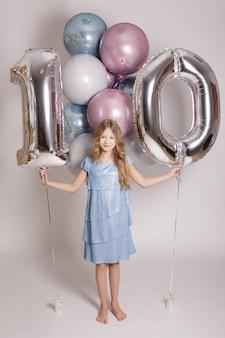 Geburtstagskonzept - mädchen mit pastellluftballons und folie zehn nummer auf weißem hintergrund