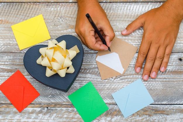 Geburtstagskonzept mit geschenkbox, umschläge auf hölzernem hintergrund flach legen. mann, der grußkarte mit stift schreibt.