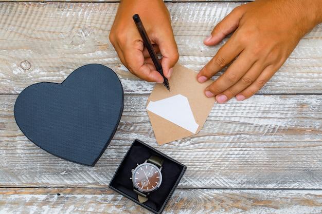 Geburtstagskonzept mit geschenkboxen, uhr auf hölzernem hintergrund flach legen. mann, der grußkarte mit stift schreibt.