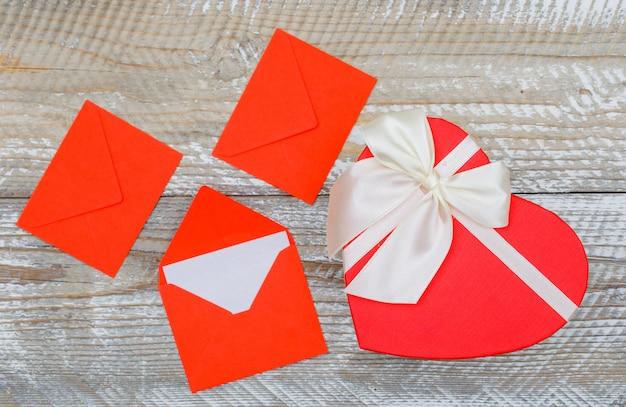 Geburtstagskonzept mit umschlägen, geschenkbox auf holzhintergrund flach legen.