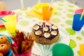 Geburtstagskuchen auf Tabelle mit farbigen Gläsern
