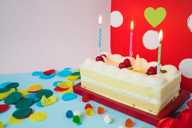 Geburtstagskuchen mit belichteten kerzen und süßigkeiten
