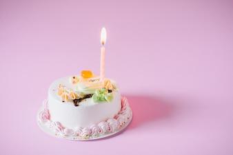 Geburtstagskuchen mit Kerzen auf farbigem Hintergrund