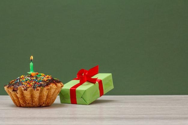 Geburtstagskuchen mit schokoladenglasur und karamell, dekoriert mit brennender festlicher kerze und geschenkbox auf grünem hintergrund. alles gute zum geburtstag minimales konzept.