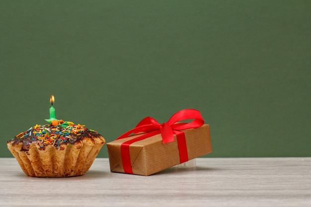 Geburtstagskuchen mit schokoladenglasur und karamell, dekoriert mit brennender festlicher kerze und geschenkbox mit rotem band auf grünem hintergrund. alles gute zum geburtstag minimales konzept.