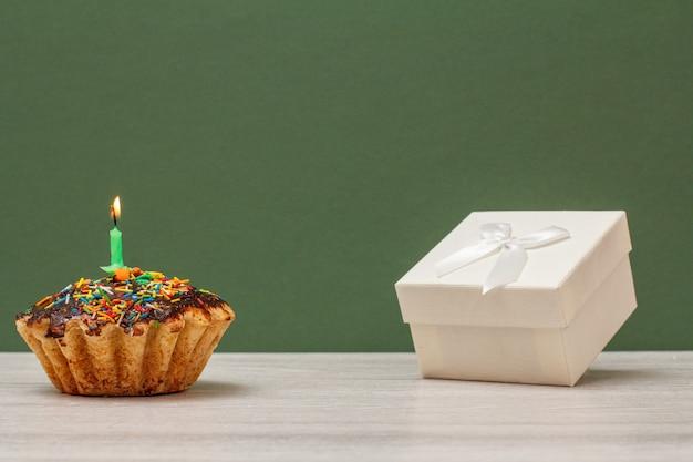 Geburtstagskuchen mit schokoladenglasur und karamell, dekoriert mit brennender festlicher kerze und weißer geschenkbox auf grünem hintergrund. alles gute zum geburtstag minimales konzept.