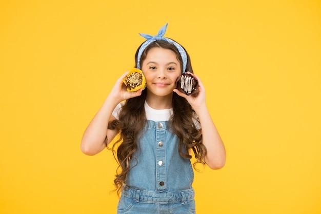 Geburtstagskuchen. süßigkeitenladen. bäckerei- und konditoreikonzept. süßes zahnkonzept. retro-mädchen muffin gelber hintergrund. glückliches kind liebt desserts. gesunde ernährung und ernährung. mehr kalorien.