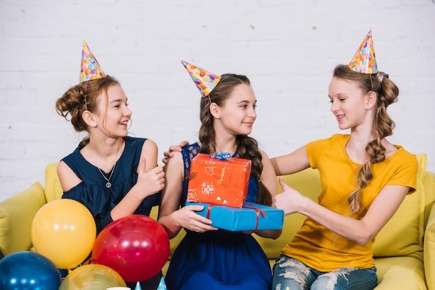 Geburtstagsmädchen, das mit ihren freunden hält geschenke in der hand sitzt