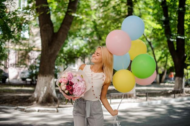 Geburtstagsmädchen mit einem blumenstrauß von blumen und von ballonen