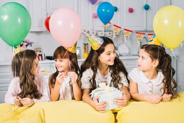 Geburtstagsmädchen, welches zu hause die party mit ihren freunden genießt