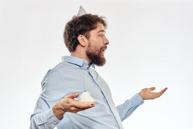 Geburtstagsmann mit einem cupcake und einer kerze in einem partyhut