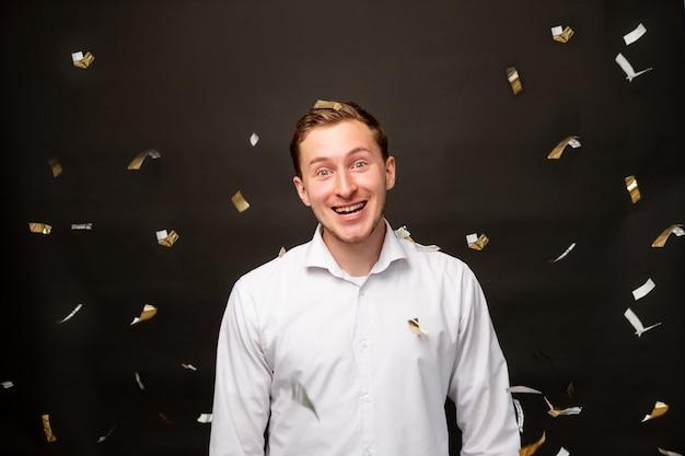 Geburtstagsmannportrait. urlaubsüberraschung. erstaunter kerl, der im konfettiregen lächelt, isoliert auf schwarzem hintergrund.