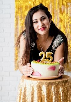 Geburtstagsparty. attraktive kaukasische frau im schwarzen partykleid bereit, geburtstagstorte zu essen, die ihren fünfundzwanzigsten geburtstag feiert