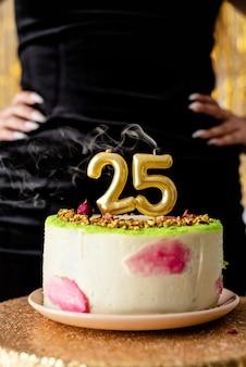 Geburtstagsparty. frau im schwarzen partykleid bereit, geburtstagstorte zu essen, die ihren fünfundzwanzigsten geburtstag feiert