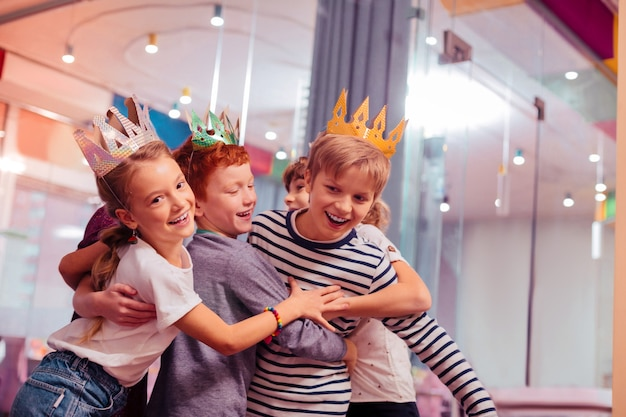 Geburtstagsparty. glückliches mädchen, das lächeln auf ihrem gesicht hält, während es ihre klassenkameraden umarmt Premium Fotos