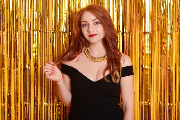 Geburtstagsparty. junge lächelnde frau lokalisiert über goldenem lametta-raum, der ereignis feiert, trägt elegantes schwarzes modekleid