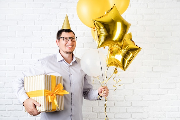 Geburtstagsparty. lustiger junger mann, der geburtstagshut hält, der ballons und eine große geschenkbox hält, die geburtstag über weißem backsteinhintergrund mit kopienraum feiert