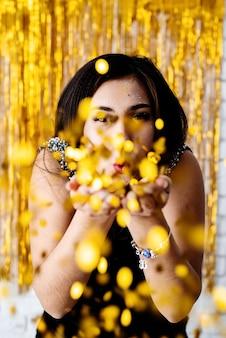 Geburtstagsparty. porträt des jungen schönen mädchens, das goldenes konfetti auf feiertagsfeier bläst