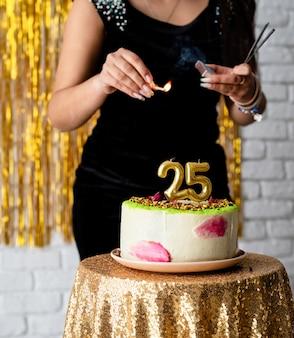 Geburtstagsparty. schöne brünette frau im schwarzen partykleid, das ihren geburtstag feiert, zündet die kerzen 25 auf dem kuchen an
